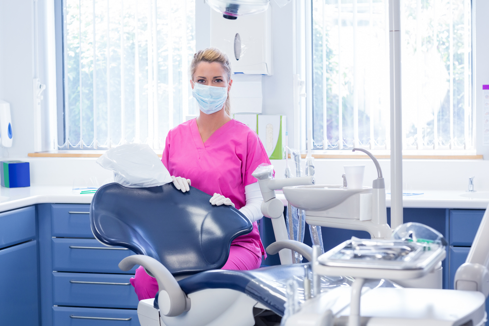 Dentist in mask looking at camera beside chair at the dental clinic